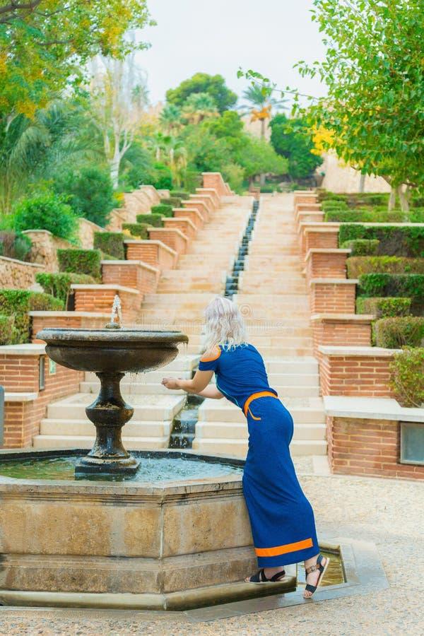 A menina toca na água em uma fonte antiga imagem de stock royalty free