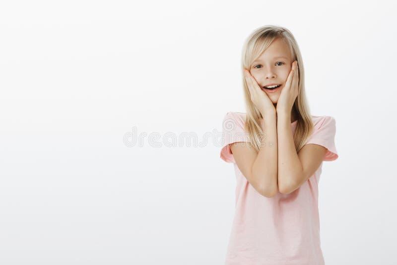 Menina tocada vendo o pônei bonito Tiro interno da criança fêmea adorável satisfeito com cabelo louro, guardando as mãos sobre imagem de stock