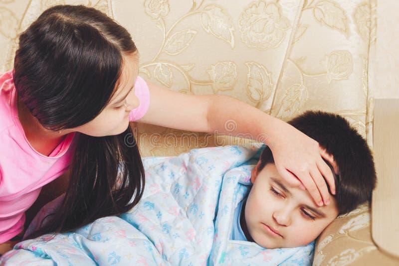 A menina tocou em seu irmão doente da testa, verifica a temperatura fotos de stock