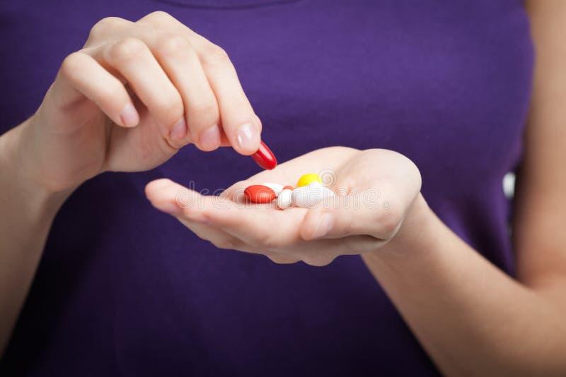 A menina toma antibióticos foto de stock