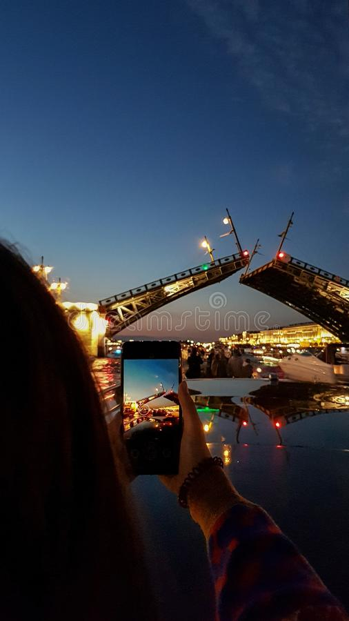 A menina toma a foto na ponte do palácio da criação de animais do telefone em St Petersburg durante as noites brancas Vista de Ne imagens de stock royalty free