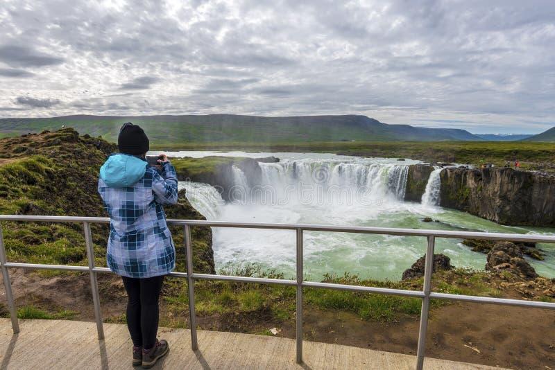 A menina toma a imagem da cachoeira de Godafoss do mirador do banco oriental fotos de stock
