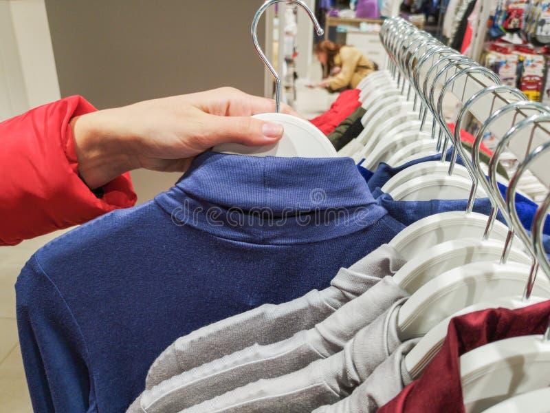 A menina toma um gancho com roupa na loja a menina escolhe coisas no gancho no close-up da loja de roupa Conceito da compra M?o d fotos de stock royalty free