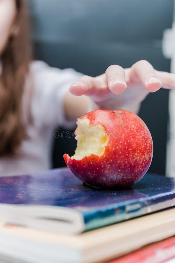a menina toma um petisco da maçã durante lições foto de stock royalty free