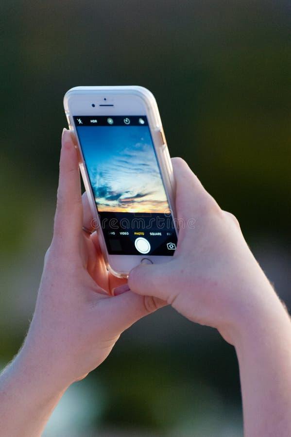 A menina toma uma foto de um por do sol colorido bonito em seu telefone fotografia de stock royalty free
