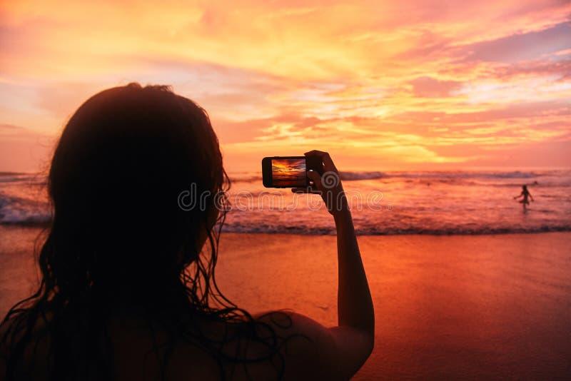 A menina toma uma foto do por do sol no telefone fotos de stock