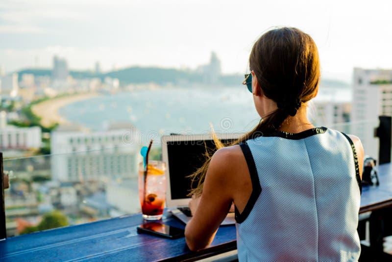 A menina trabalha em um computador em um café no telhado Escrita fêmea em um portátil em um café do telhado, sentando-se em um de fotos de stock