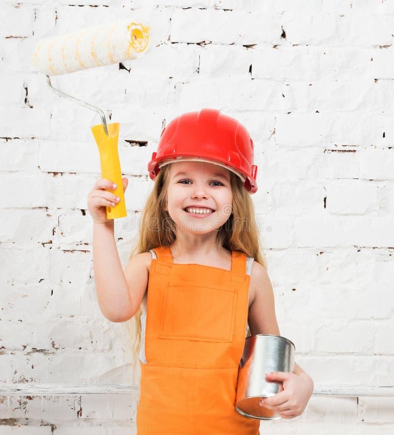 Menina-trabalhador pequeno com pintura e rolo nas mãos imagem de stock