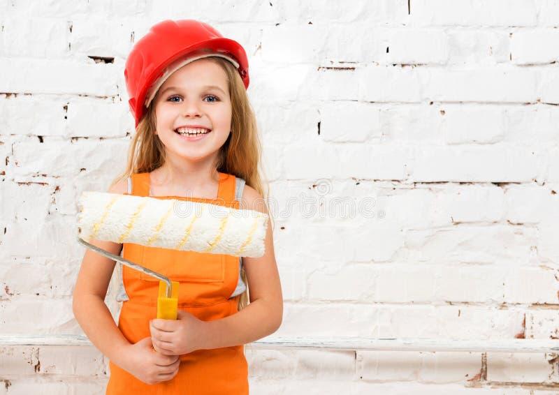 Menina-trabalhador pequeno com rolo de pintura imagem de stock royalty free
