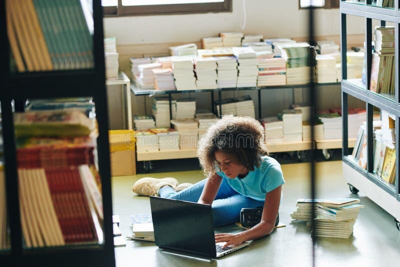 Menina Trabalhando Em Laptop Na Biblioteca foto de stock