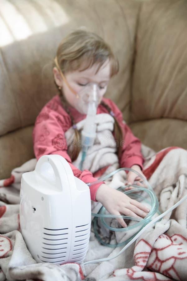 A menina trata um nariz ralo usando um nebulizer, tratamento em casa fotos de stock