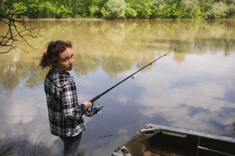 A menina trava peixes no rio fotos de stock royalty free