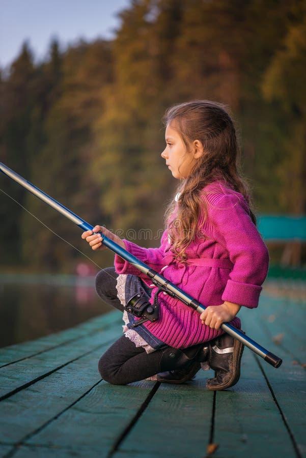A menina trava a vara de pesca imagens de stock