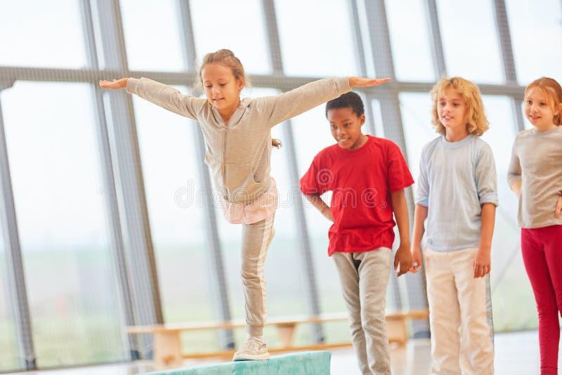 A menina treina o equilíbrio no feixe de equilíbrio fotografia de stock royalty free