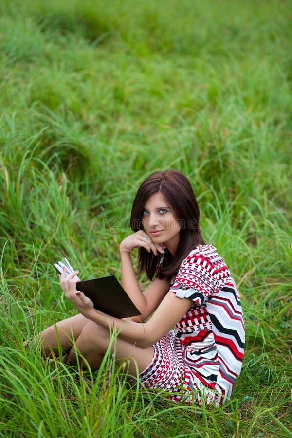 Menina triguenha bonita no livro de leitura do parque fotos de stock