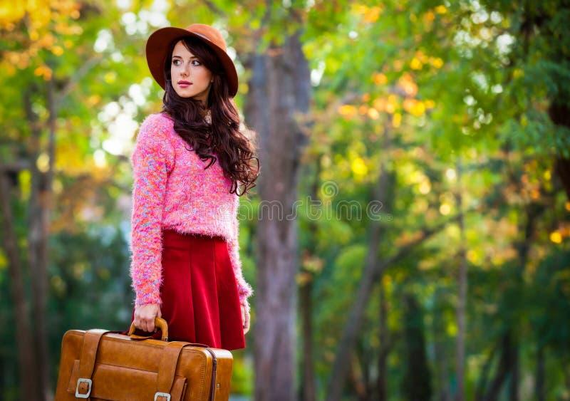 Menina triguenha com a mala de viagem no parque imagem de stock royalty free