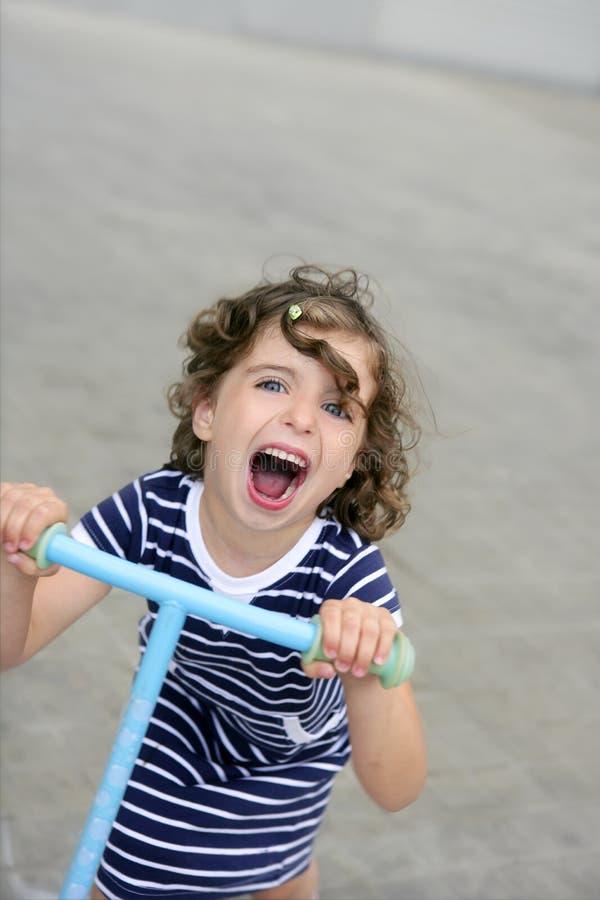 Menina triguenha com o 'trotinette' na cidade imagens de stock royalty free
