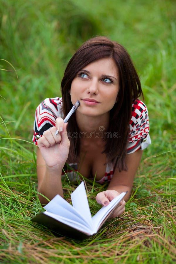 Menina triguenha com pensamento do caderno e da pena foto de stock