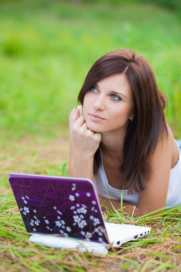 Menina triguenha do estudante no parque com caderno imagens de stock royalty free