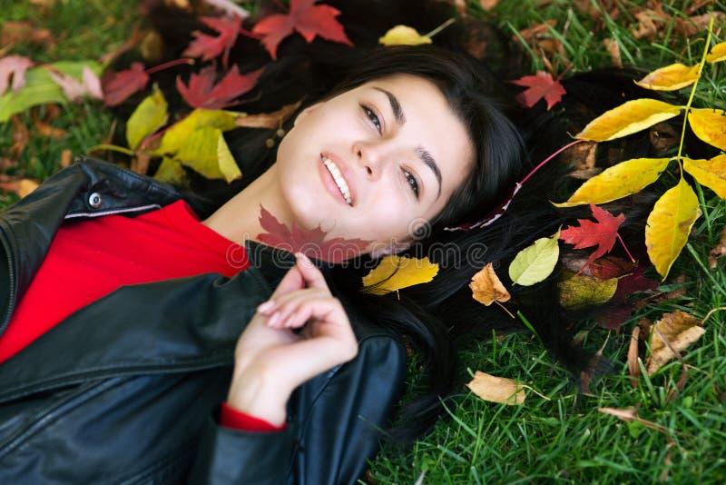 Menina triguenha e folhas douradas imagens de stock royalty free