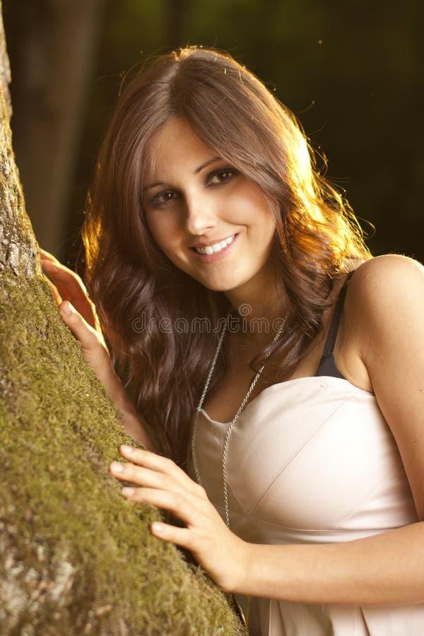 Menina triguenha feliz em uma floresta mágica no musgo fotos de stock royalty free