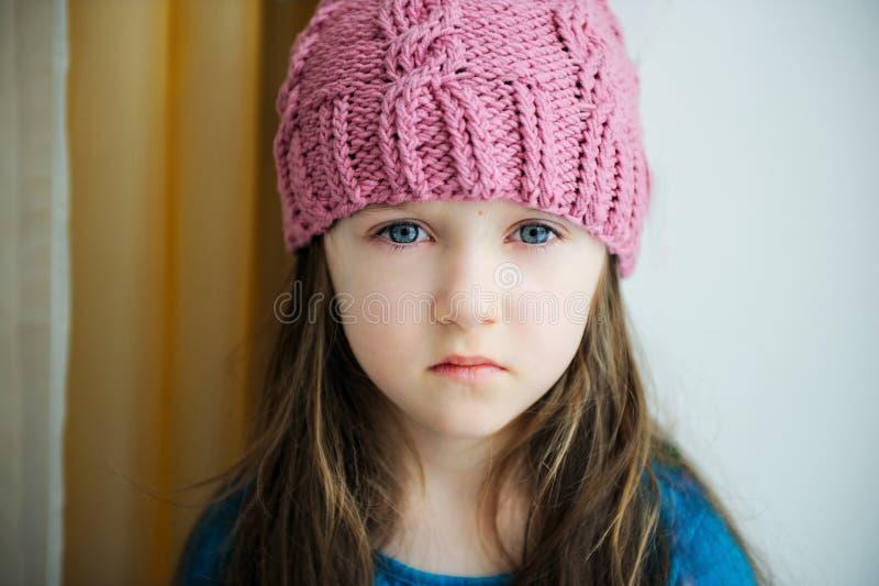 Menina triste adorável da criança no chapéu feito malha cor-de-rosa fotos de stock