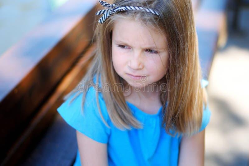 Menina triste adorável que sonha e que pensa sobre a parte externa futura imagens de stock royalty free