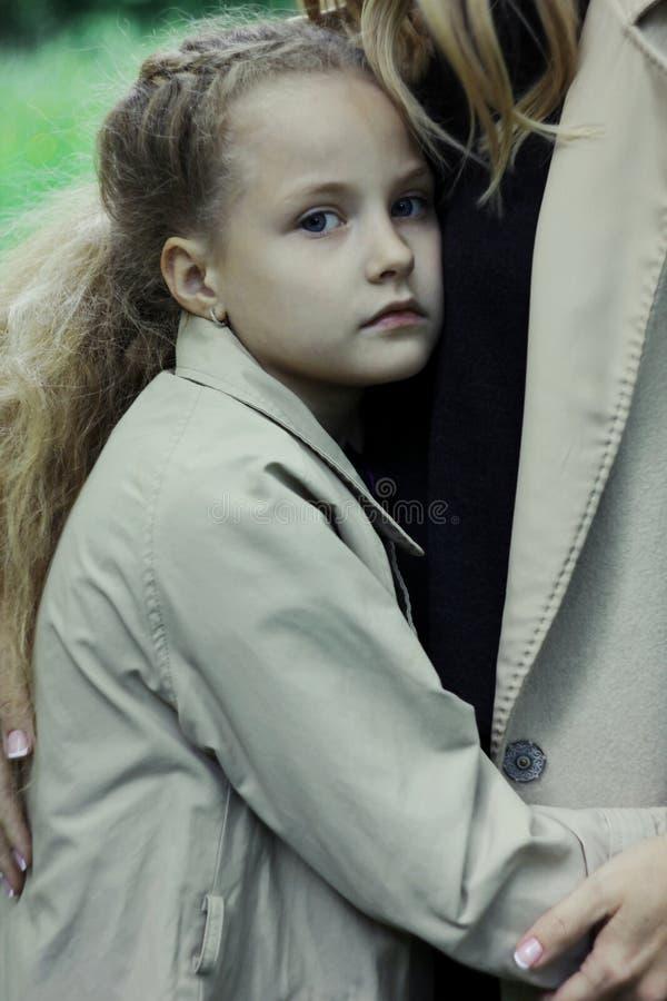 Menina triste 7 anos velha com os olhos azuis que olham a câmera fotos de stock