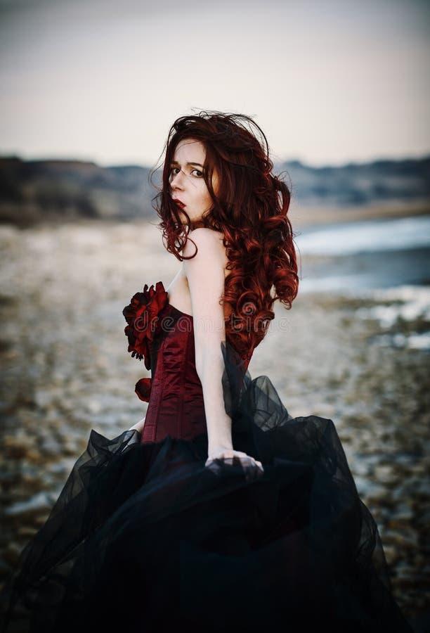 Menina triste bonita do goth que está na costa de mar Vista traseira fotos de stock