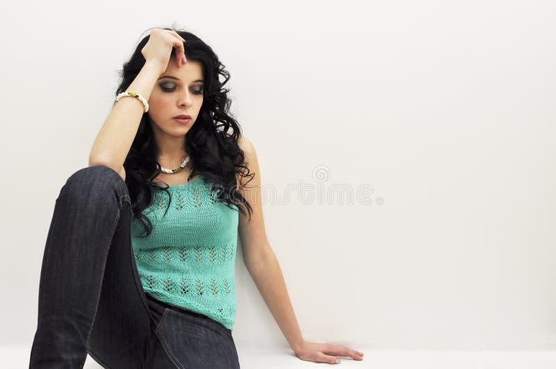 Menina triste bonita nova que senta-se no assoalho fotos de stock