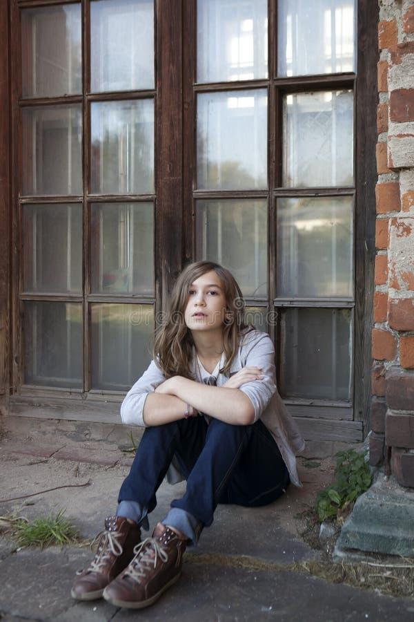 A menina triste com cabelo longo nas calças de brim de treze senta-se perto da janela grande imagem de stock