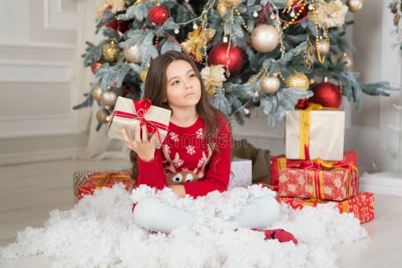 a menina triste comemora o feriado de inverno Ano novo feliz Tempo do Natal Menina bonito da criança pequena com presente do xmas imagem de stock