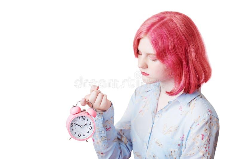 Menina triste do adolescente com o despertador cor-de-rosa da terra arrendada do cabelo fotos de stock royalty free