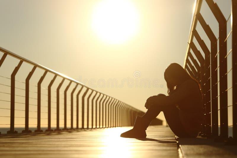 A menina triste do adolescente comprimiu o assento em uma ponte no por do sol fotografia de stock