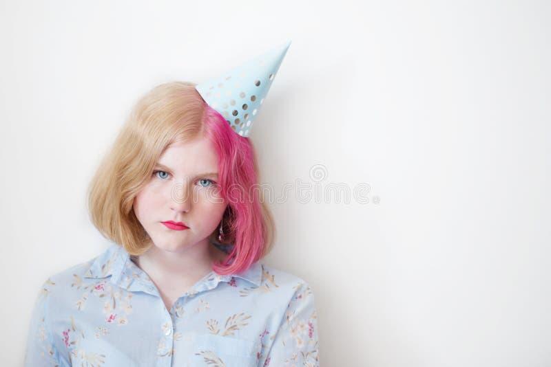 Menina triste do adolescente no chapéu do aniversário foto de stock