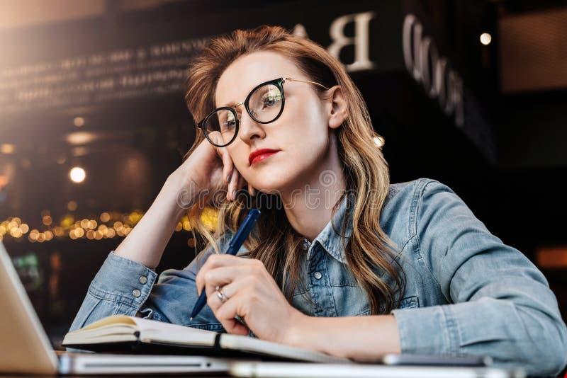 Menina triste do estudante que senta-se no café na frente do portátil que prepara-se para exames A mulher toma curso de formação  fotos de stock