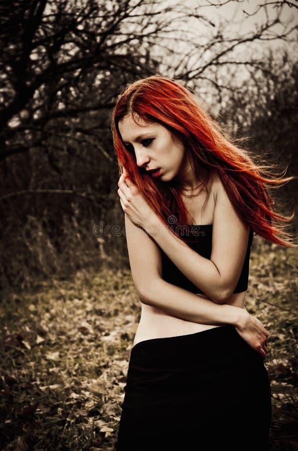 Menina triste do redhead bonito entre as árvores do outono foto de stock