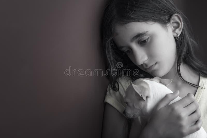 Menina triste e só e seu cão pequeno fotografia de stock royalty free