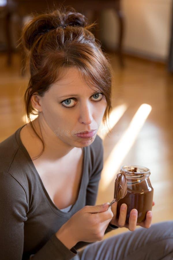 A menina triste está comendo a propagação do chocolate fotos de stock