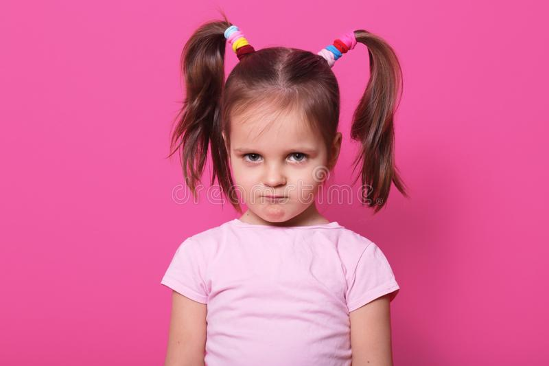 A menina triste está contra a parede cor-de-rosa, olha a câmera A criança bonito veste a camisa cor-de-rosa de t, tem duas caudas fotos de stock
