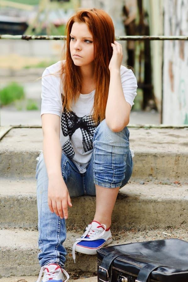 Menina triste nova bonita que senta-se na escadaria fotos de stock