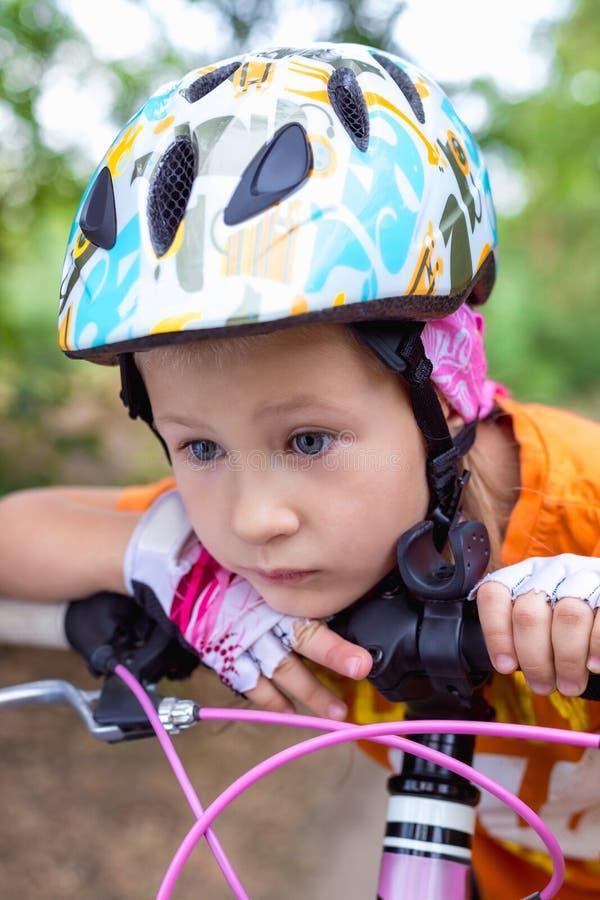 Menina triste pequena bonito em um capacete com uma bicicleta no ver?o imagens de stock