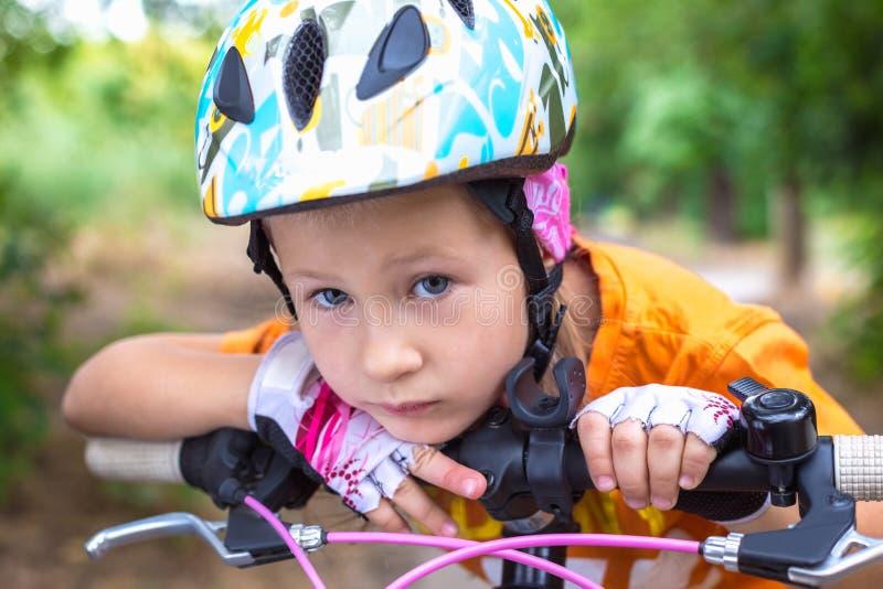 Menina triste pequena bonito em um capacete com uma bicicleta no ver?o fotos de stock royalty free
