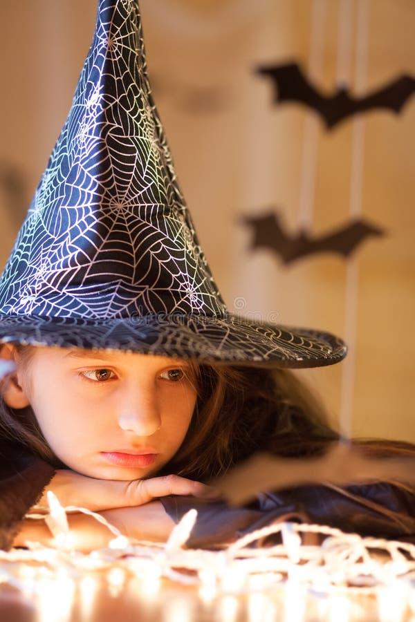 Menina triste pequena no traje da bruxa, o Dia das Bruxas imagem de stock royalty free