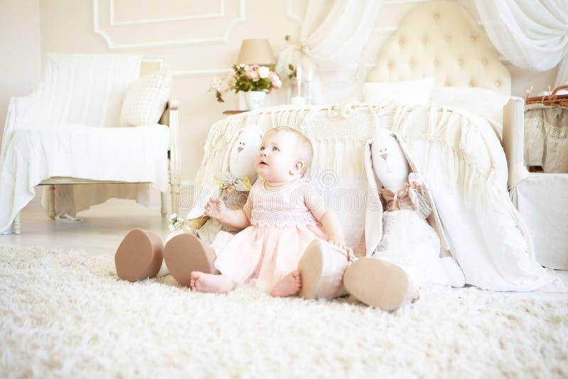 A menina triste pequena que senta-se entre coelhos do brinquedo aproxima a cama fotos de stock