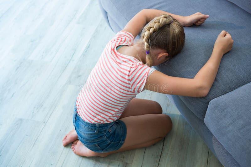 Menina triste que ajoelha-se pelo sofá em casa foto de stock