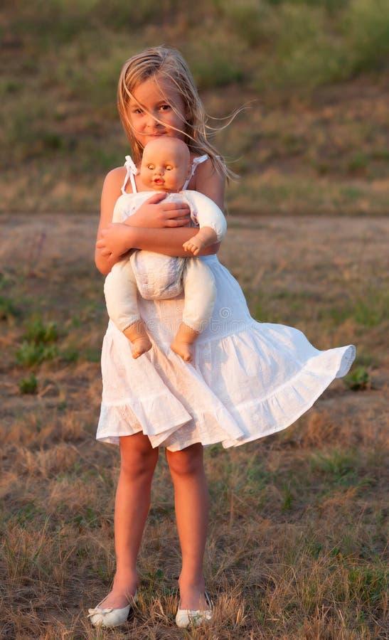 Menina triste que está sozinha e que prende seu brinquedo foto de stock