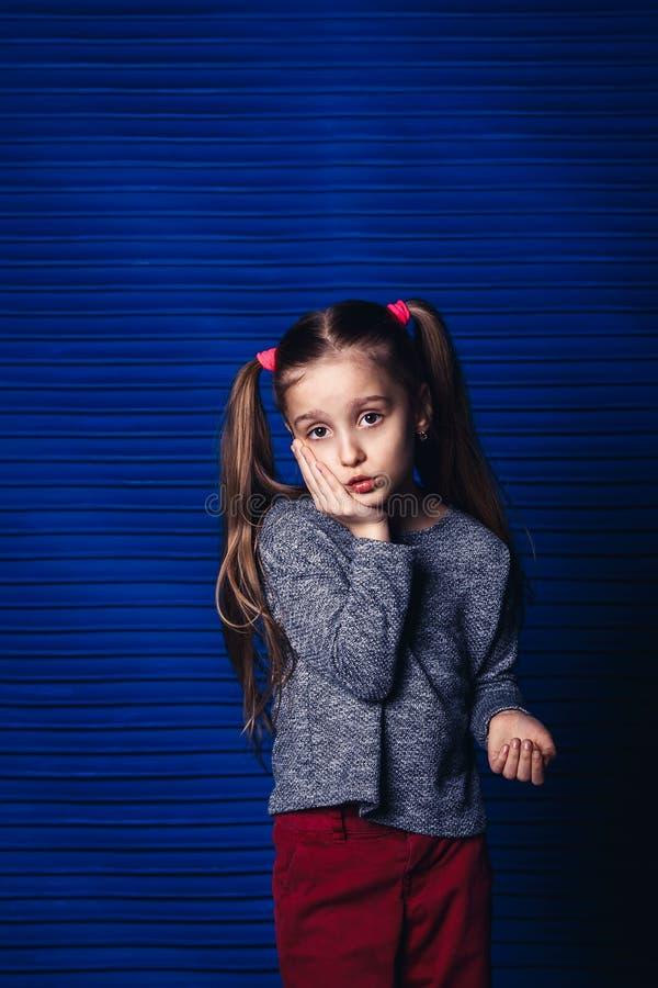 Menina triste que guarda seu mordente em um fundo azul conceito da dor de dente da criança imagens de stock