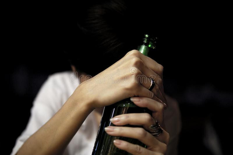 Menina triste que guarda uma garrafa da cerveja imagens de stock