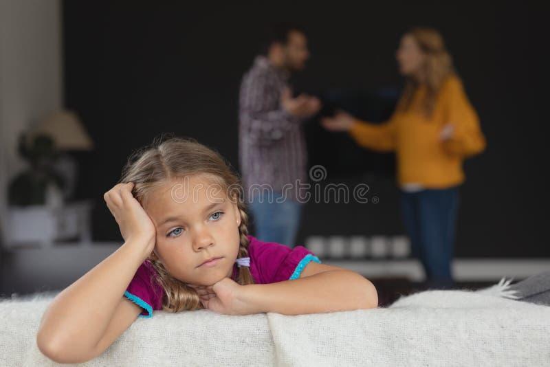 Menina triste que inclina-se no sofá quando pais que discutem no fundo imagens de stock